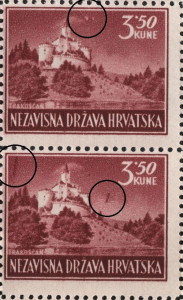 Two spots in the sky above the castle, close to the upper frame (the upper stamp)